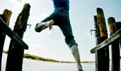 Eine Frau, die von einem Steg in einen See springt
