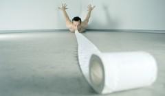 witziges Foto zum papierlosen Büro. Einem Mann hängt eine Rolle Toilettenpapier aus dem Mund